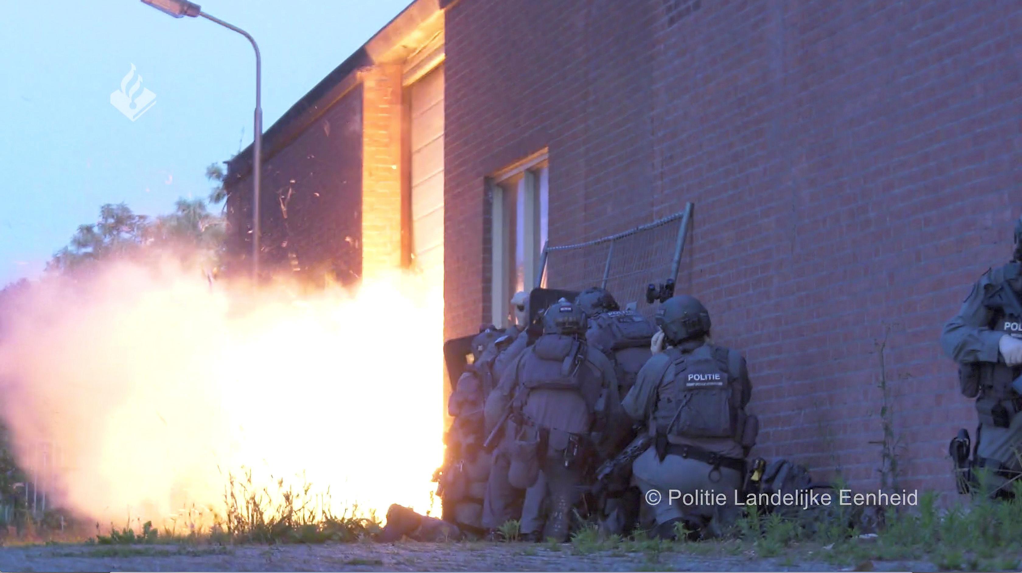 Eine Polizeispezialeinheit sprengt den Eingang einer Lagerhalle auf.