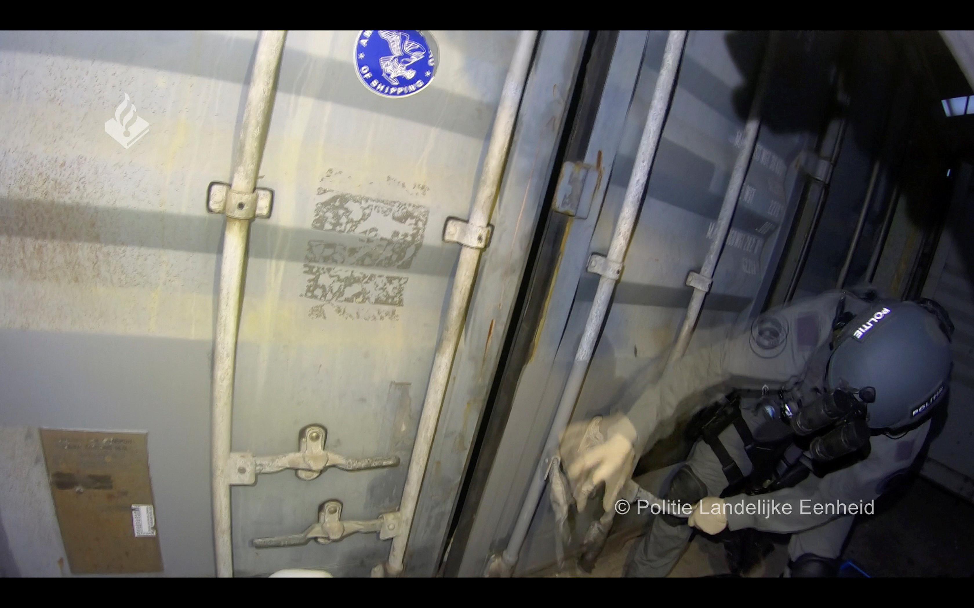 Die Polizei bricht einen Container auf.