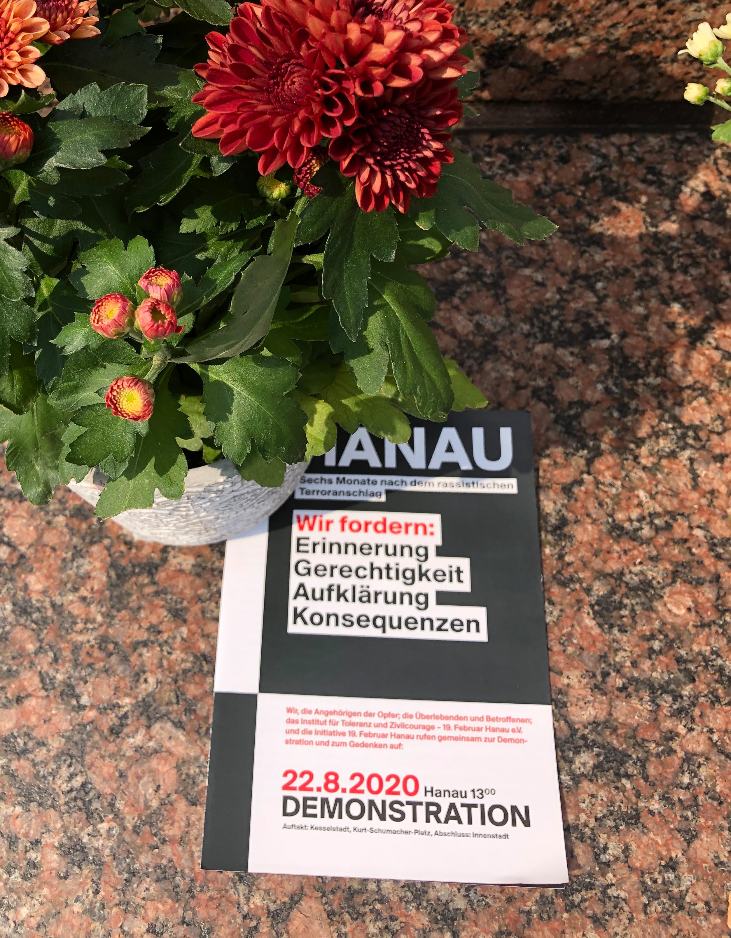 11.08.2020, Hessen, Hanau: Der Aufruf zu einer Gedenk- und Demonstrationsveranstaltung für die Opfer des rassistisch motivierten Anschlags in Hanau vom 19. Februar liegt unter Blumen am Brüder Grimm-Denkmal.